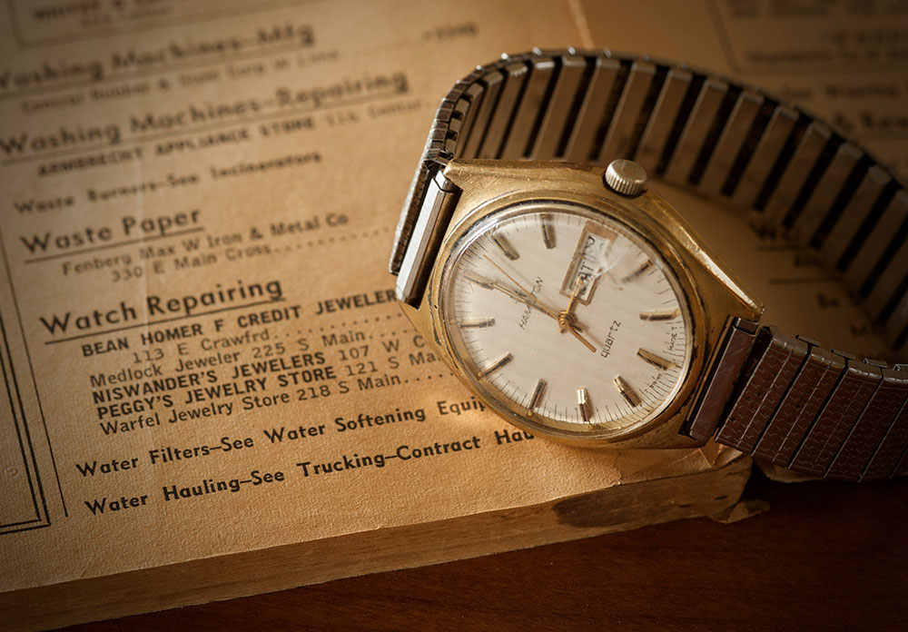 Vintage and Golden Watch Photographed with Repair Advertisement